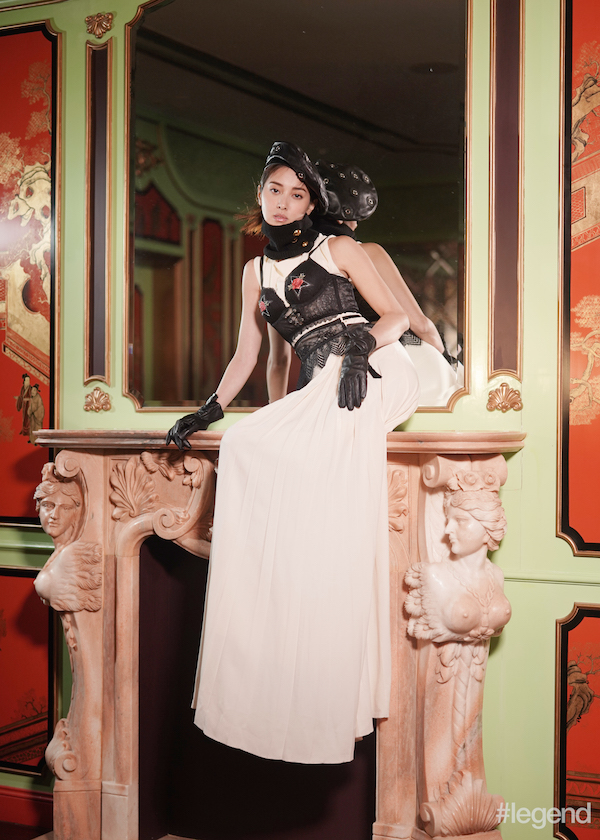 Black leather beret with metal eyelets and gloves by Claudie Pierlot; black knitted scarf by Sacai; ivory silk gown by Lanvin; black corset bra with rose appliqué and black garter by Intimissimi