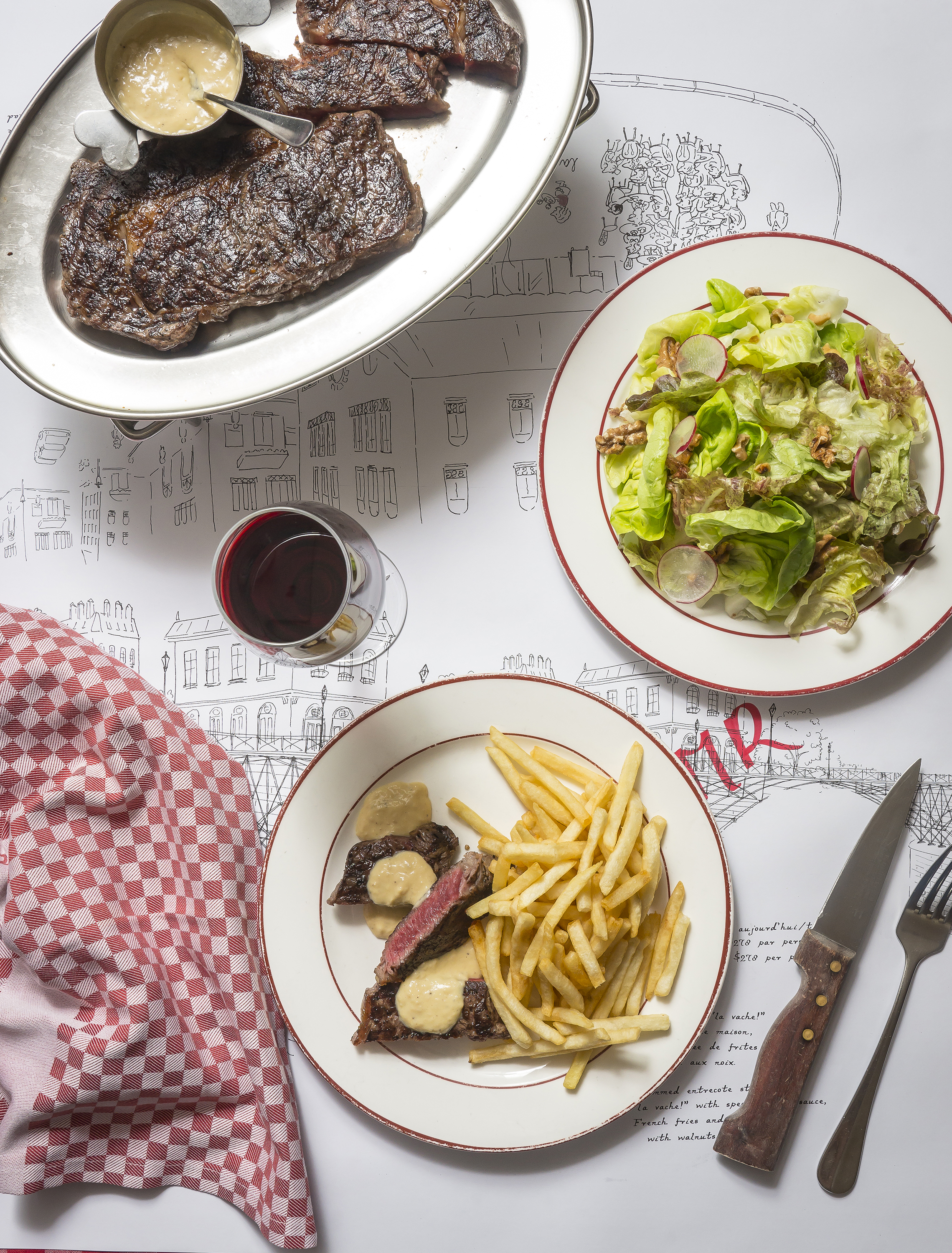The signature ribeye steak with salad and fries