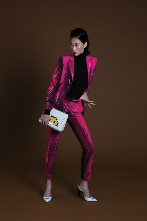Angie Ng wears suit and shoes by Moschino. bag by Anya Hindmarch and jewellery by Van Cleef & Arpels