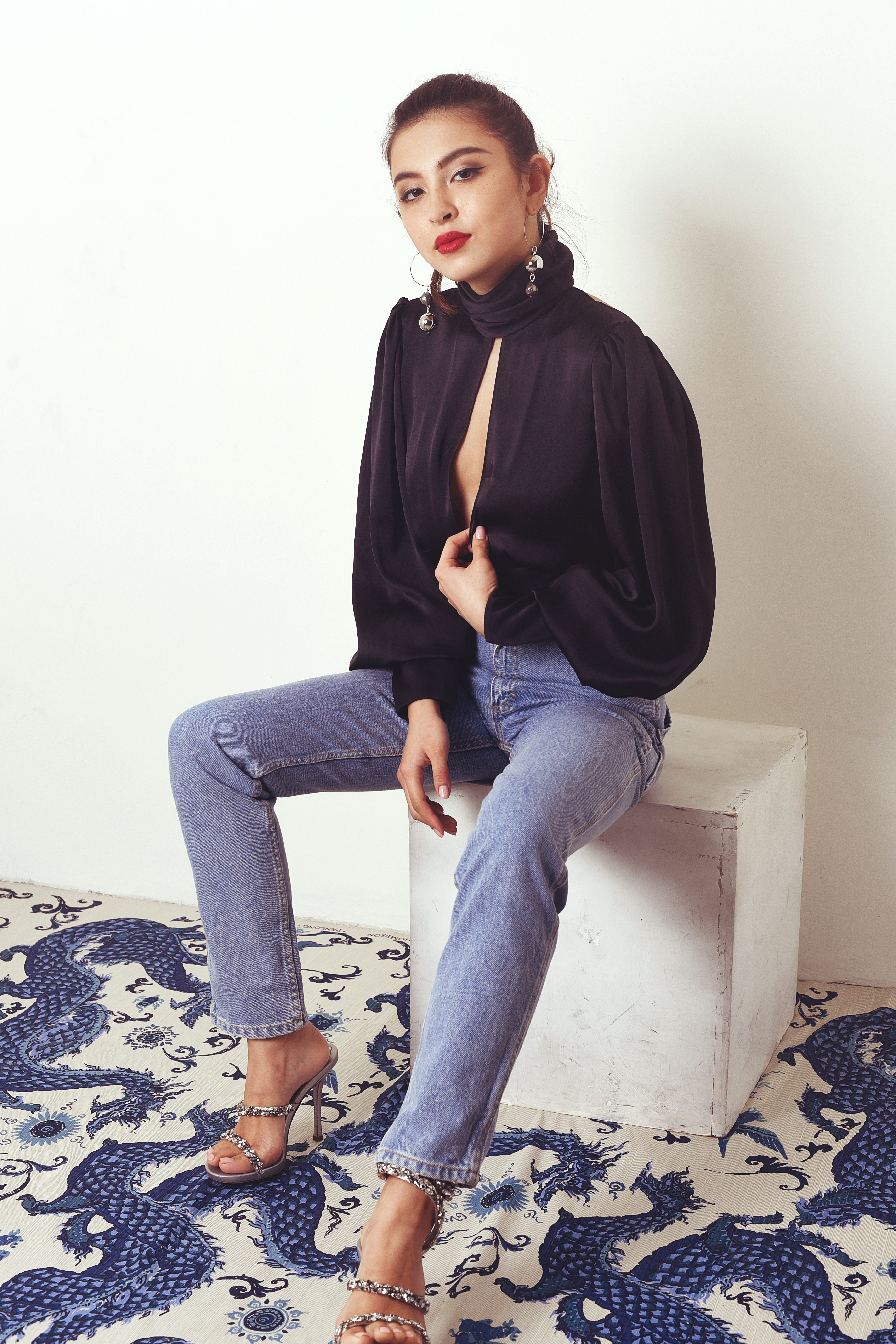 Night Out top by Orseund Iris, denim by Eckhaus Latta, pearl earrings by Mounser all available at Net a Porter; heels by Rene Caovilla