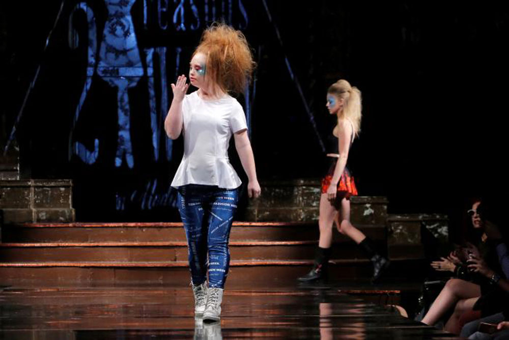 Madeline Stuart blows a kiss as she walks in her own show on Sunday (photo c/o AFP)