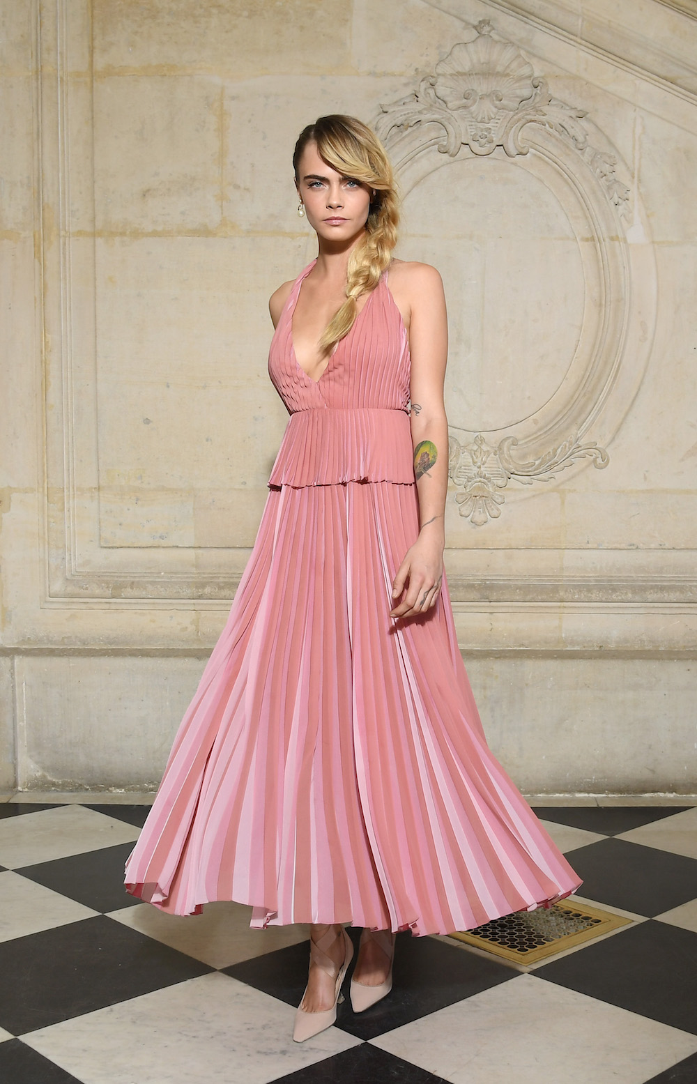 Cara Delevingne in Dior Fall 2019 pink pleated silk dress, and Dior shoes.