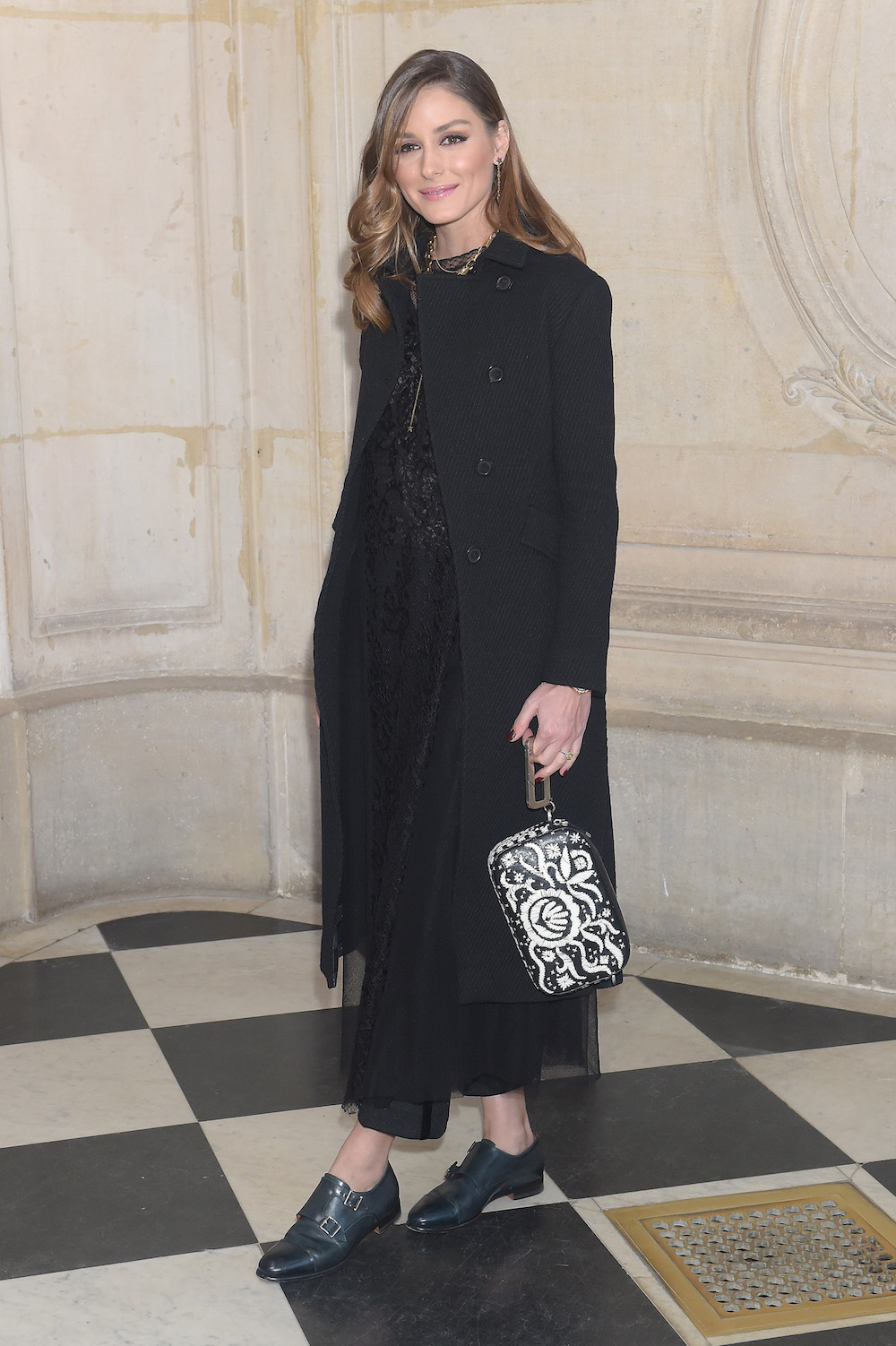 Olivia Palermo in Dior Fall 2019 black wool coat, a Dior Fall 2019 black lace dress, a Diorquake black printed leather clutch and Dior shoes.